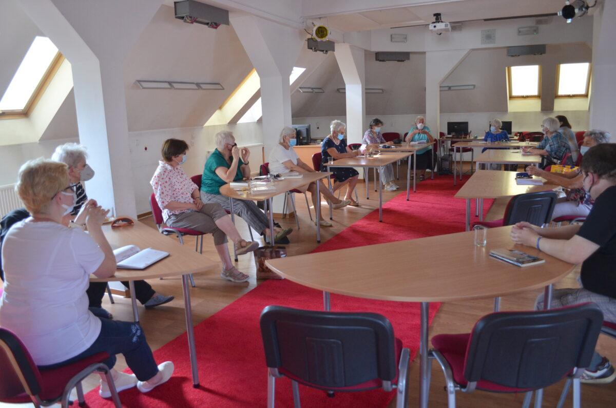 Grupa uczestników klubu książki rozmawia o przeczytanych tytułach